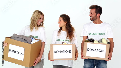 Team of volunteers smiling at camera holding donations boxes