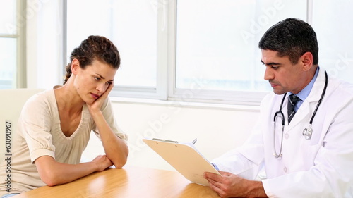 Doctor speaking with his sick patient at desk