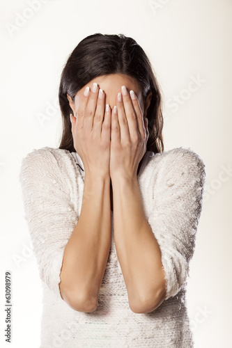 embarrassed girl covers her face with her palms