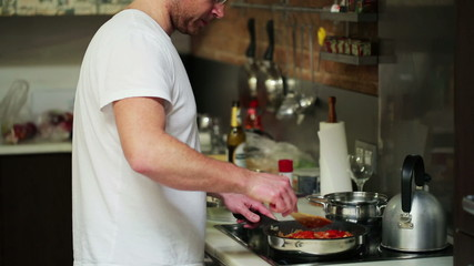 Young man preparing and tasting dinner in his kitchen