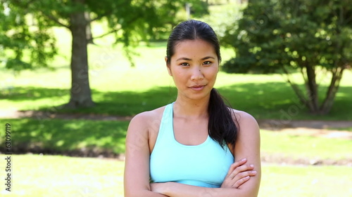 Fit asian girl smiling at camera with arms crossed