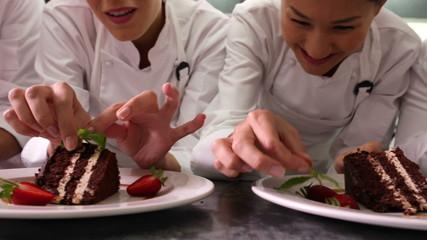 Line of chefs garnishing dessert plates