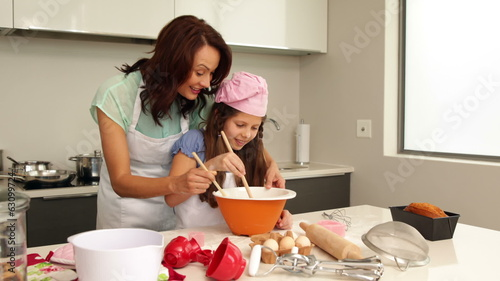 Mother showing her daughter how to bake