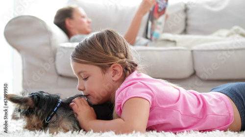 Little girl playing with puppy with her mother reading