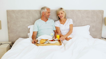 Couple chatting and having breakfast in bed