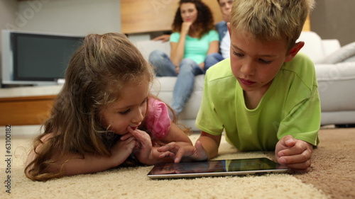 Sibings lying on floor using tablet with parents