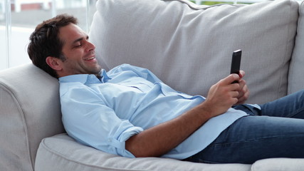 Casual man lying on the sofa sending a text message