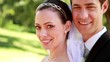 Attractive newlyweds smiling at camera while embracing