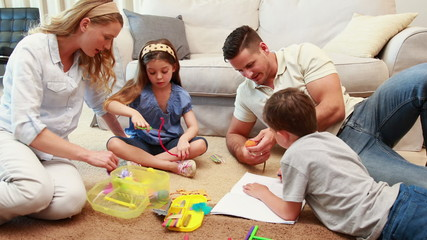 Young siblings doing arts and crafts on the rug with parents