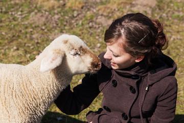 junge Frau und kleines Lamm sehen sich an