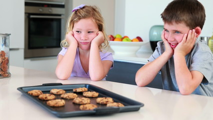 Siblings waiting for hot cookies to cool down