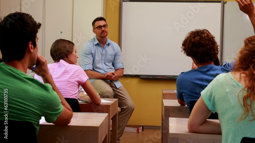 Lecturer sitting and speaking to his students in classroom