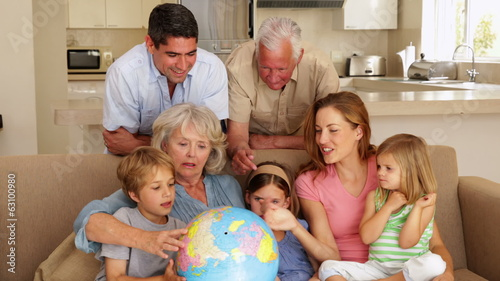 Extended family looking at globe together on couch