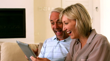 Couple using their tablet together on the couch