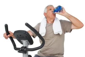 Senior man drinking water on stationary bike