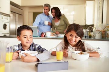Hispanic Family Eating Breakfast Using Digital Devices