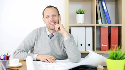 Smiling young architect over blueprints in the office