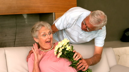 Senior man surpising partner with flowers on the couch