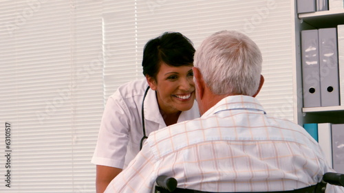 Nurse talking to an old man in a wheelchair
