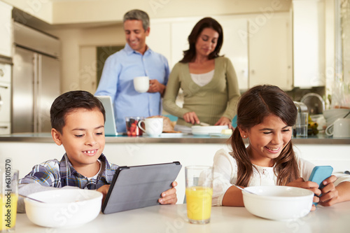 Hispanic Family Eating Breakfast Using Digital Devices