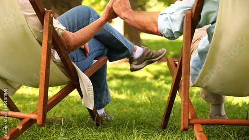 Retired couple sitting in deck chairs holding hands