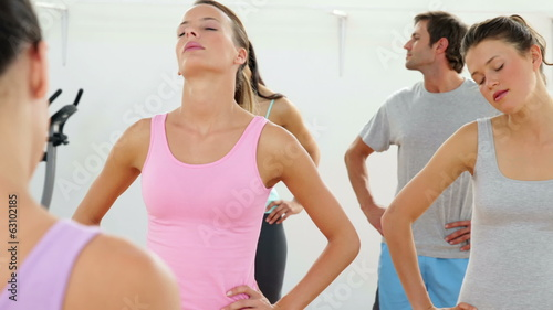 Class doing yoga together in studio