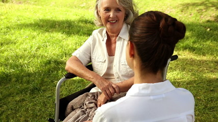 Nurse talking to woman in wheelchair outside