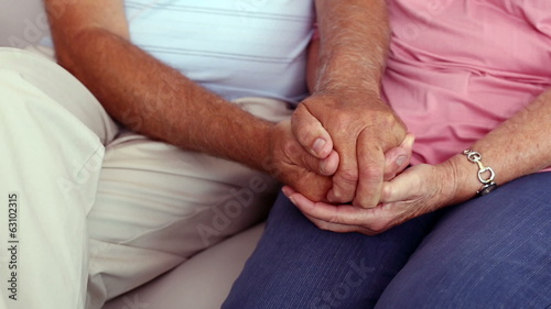 Senior couple holding hands on the couch