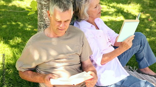 Retired couple leaning against tree reading