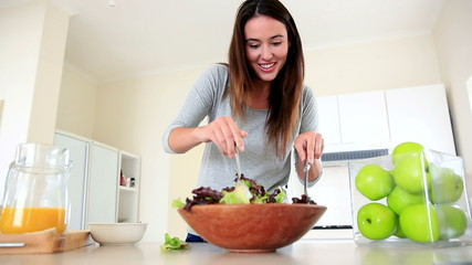 Pretty brunette preparing a healthy salad