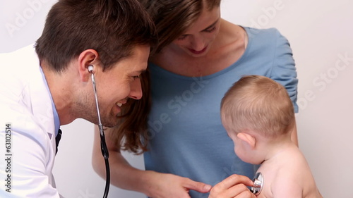 Pretty mother holding baby boy while pediatrician listens to