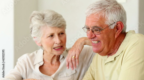 Senior couple sitting at the table using tablet pc