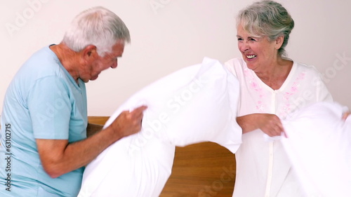 Senior couple having a pillow fight