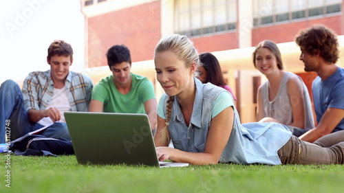 Blonde student using laptop with classmates sitting behind