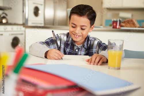 Hispanic Boy Doing Homework At Table