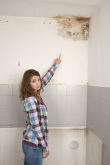 Woman points to a mould spot on the wall