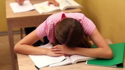 Student sleeping on desk during class
