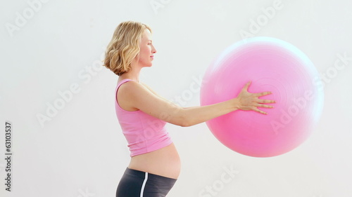Pregnant blonde holding exercise ball