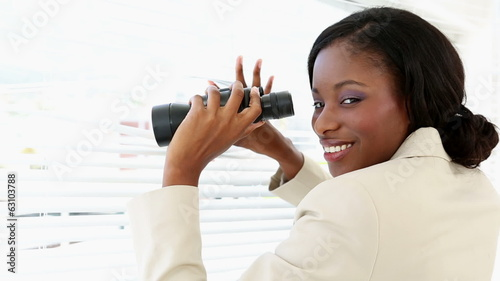 Businesswoman looking through blinds with binoculars