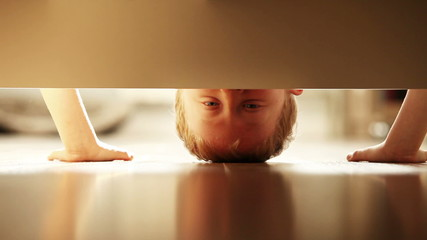 Cheerful little boy look under the bed and sincerely smiling