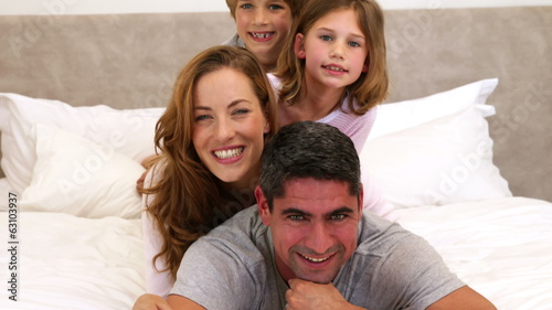Cute parents and children lying on bed smiling at camera