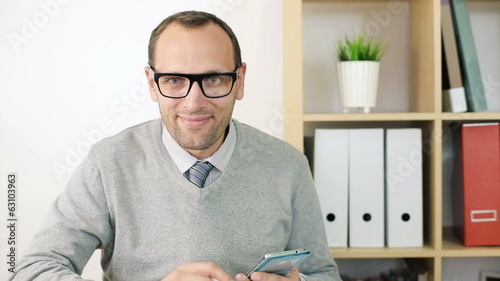 Smiling, happy young businessman with smartphone in the office