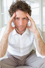 Worried well dressed man sitting with head in hands