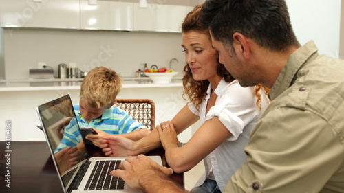 Parents using laptop while their son is drawing