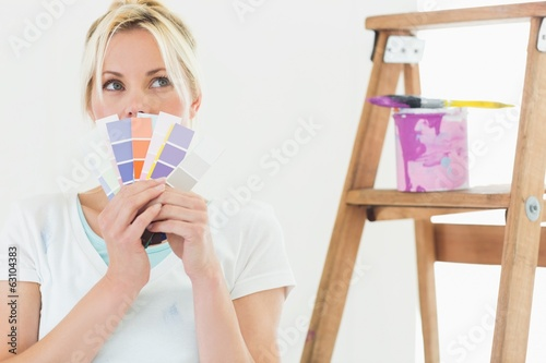 Woman holding color swatches in new house