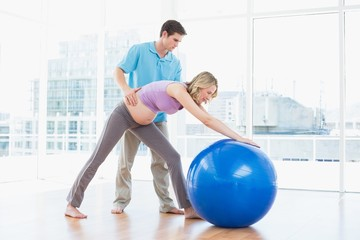 Trainer exercising with blonde pregnant client and exercise ball