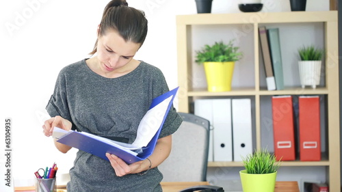 Young businesswoman reading documents in the office