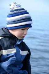 Junge mit Bommelmütze blickt aufs Meer