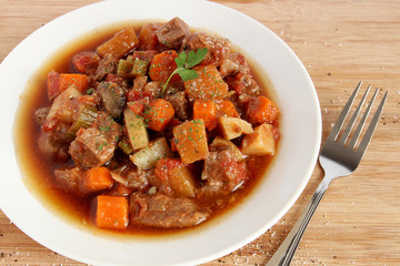 Beef stew in white plate, close-up view
