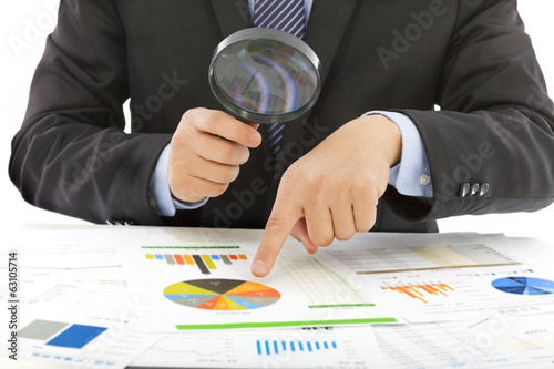 businessman hold a magnifying glass to check
